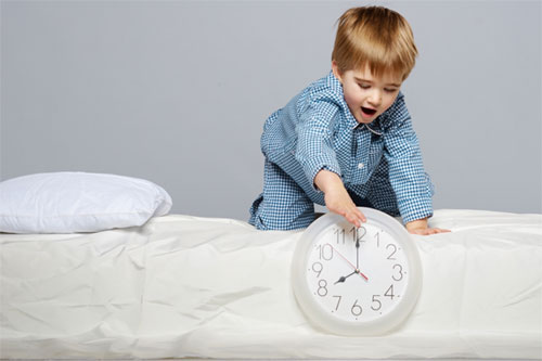Child on bed playing with clock